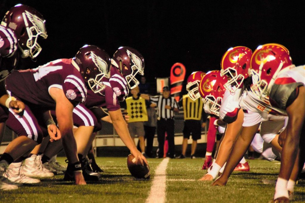Two american football teams line up against each other before the play starts